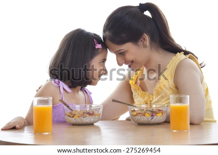 Mother and daughter having breakfast - stock photo