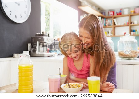 Mother And Daughter Having Breakfast At Kitchen Table - stock photo