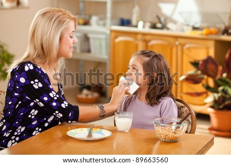 mother and daughter having breakfast: milk and cereals