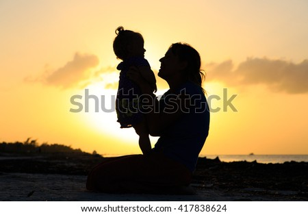 mother and daughter having fun at sunset