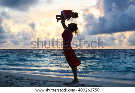 mother and daughter having fun at sunset beach - stock photo