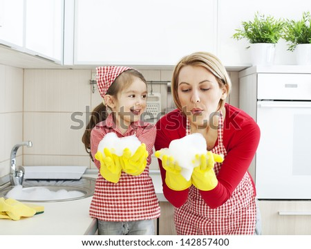 Mother and daughter having fun blowing foam in the kitchen - stock photo