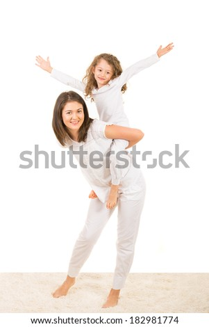 Mother and daughter having fun home and offering to her girl piggy back ride - stock photo