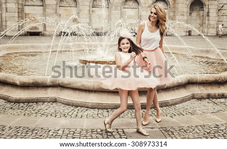 Mother and daughter having fun in same outfits wearing tutu skirts - stock photo