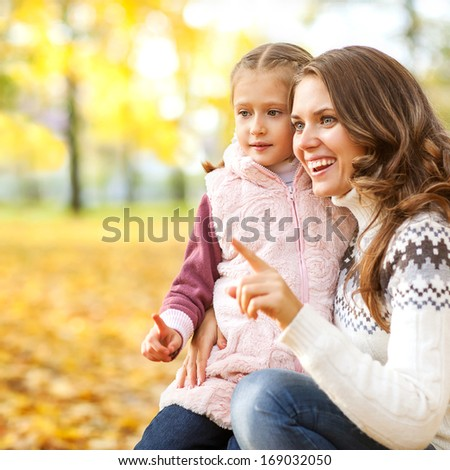 Mother and daughter having fun in the autumn park