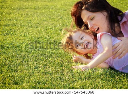Mother and daughter having fun on grass - stock photo