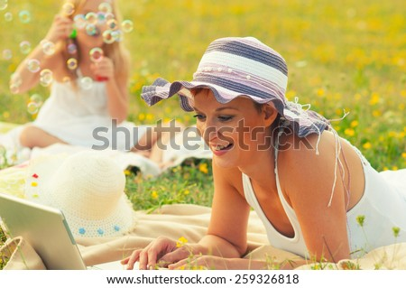 Mother and daughter having fun on the meadow on sunny spring day. - stock photo