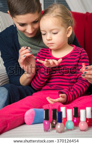 Mother and daughter having fun painting fingernails, family time concept - stock photo