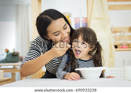 Mother and daughter having healthy breakfast in kitchen