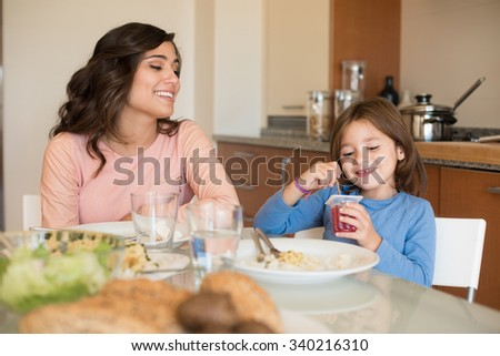 Mother and daughter having lunch in the kitchen - stock photo