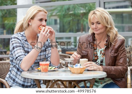 Mother and daughter having lunch together outdoors