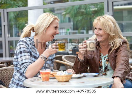 Mother and daughter having tea and coffee laughing together