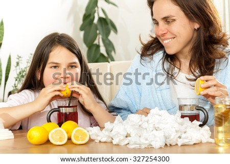 Mother and daughter having tea, eating lemon, honey to heal