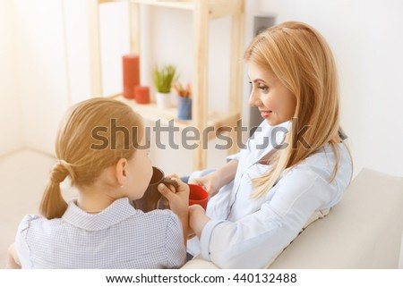 Mother and daughter having tea on sofa