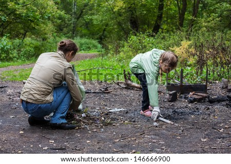 Mother and daughter helping clean up the forest in Elk Island National Park. - stock photo