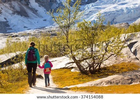 mother and daughter hiking on the lake with  mountains and the glacier Nigardsbreen at the background
