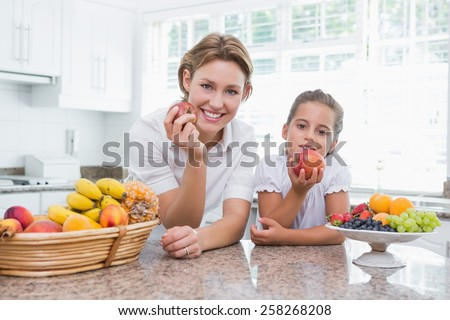Mother and daughter holding apples at home in kitchen - stock photo