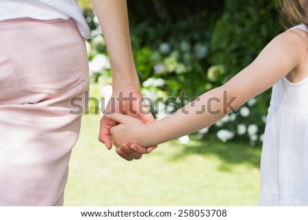 Mother and daughter holding hands outside in the garden - stock photo