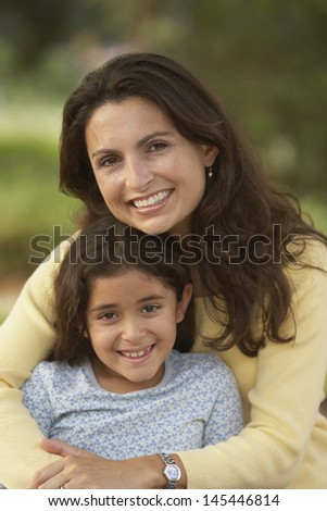 Mother and daughter hugging and smiling - stock photo