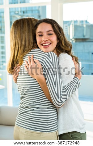 Mother and daughter hugging at home - stock photo