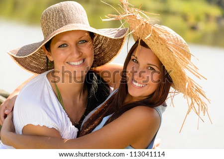 Mother and daughter hugging outdoors summer teen vacation straw hats - stock photo