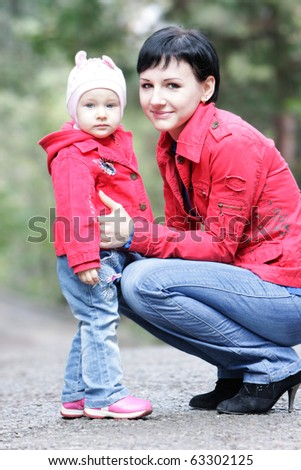 mother and daughter in autumn park - stock photo