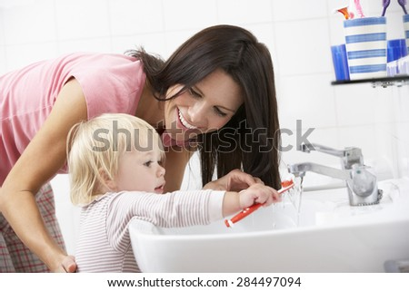 Mother And Daughter In Bathroom Brushing Teeth - stock photo