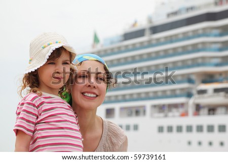 mother and daughter in dock, big cruise ship on background - stock photo