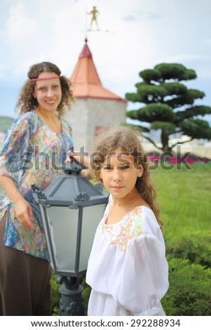 Mother and daughter in ethnic dress near the medieval castle, focus on girl  - stock photo