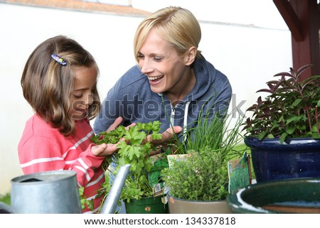 Mother and daughter in garden planting aromatic flowers - stock photo