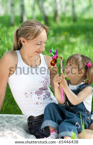 Mother and daughter in jeans with toy outdoor - stock photo