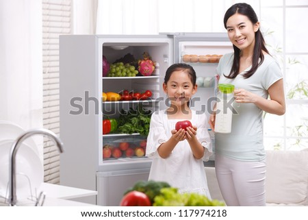 mother and daughter in kitchen - stock photo