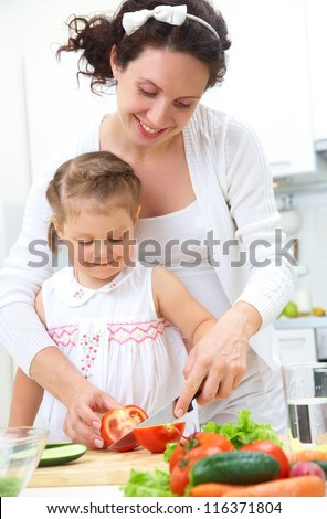 Mother and daughter in kitchen making a salad - stock photo