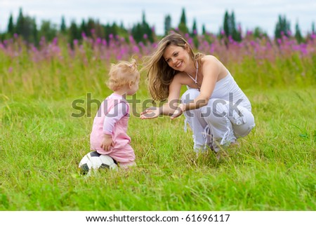 Mother and daughter in meadow outdoor - stock photo