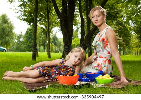 Mother and daughter in park making picnic
