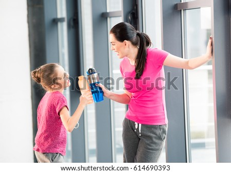 mother and daughter in pink shirts with sport bottles in gym