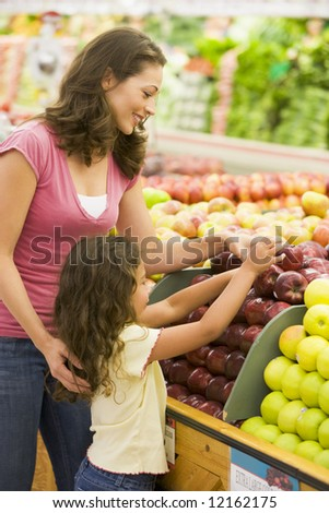 Mother and daughter in produce section of supermarket - stock photo