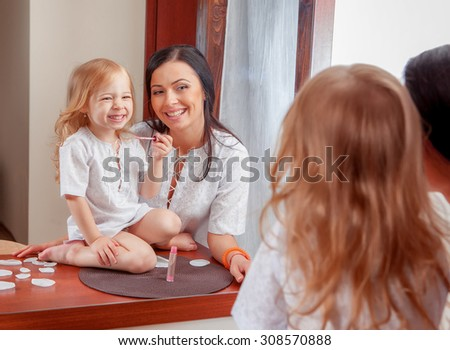 Mother and daughter in room interior near mirror - stock photo