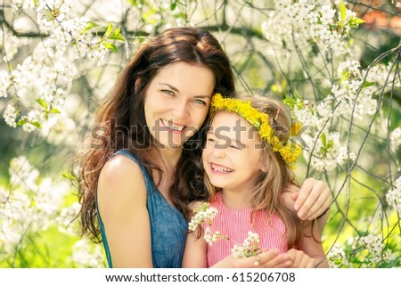 Mother and daughter in spring cherry blossom park
