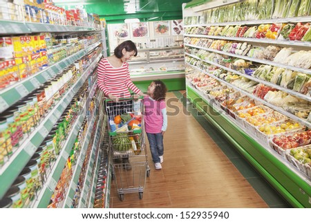 Mother and Daughter in Supermarket Shopping - stock photo