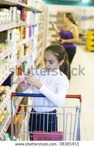 Mother and daughter in supermarket. Shopping. Girl looking for soap