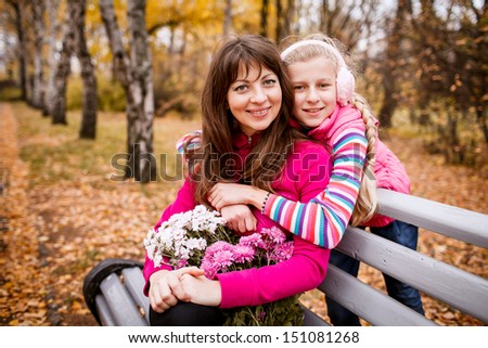 mother and daughter in the autumn garden - stock photo