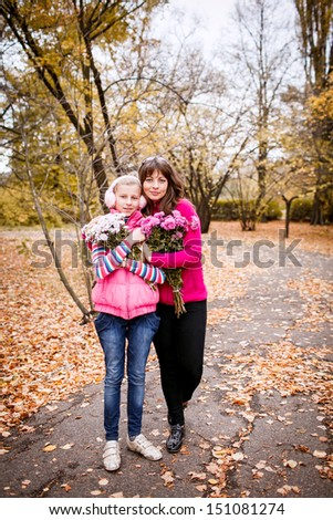 mother and daughter in the autumn garden. Full-length - stock photo