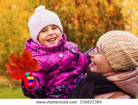 Mother and daughter in the autumn park.