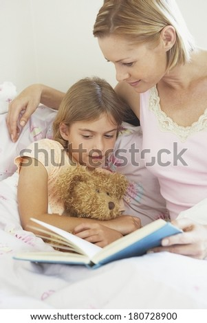 Mother and daughter in the bed reading a book