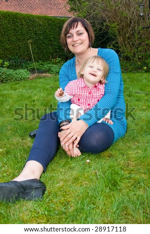 Mother and daughter in the garden. - stock photo