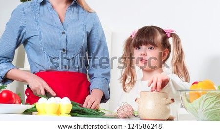 mother and daughter in the kitchen cooking - stock photo