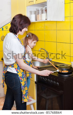Mother and daughter in the kitchen, near the plate