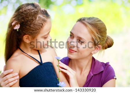 Mother and daughter in the park looking to each other - stock photo