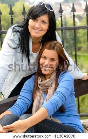 Mother and daughter in the park smiling teen together loving - stock photo